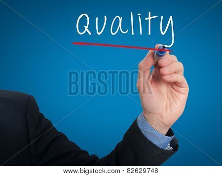 Businessman hand writing quality in the air - Stock image