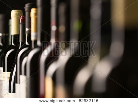 Row of vintage wine bottles in a wine cellar (shallow DOF; color toned image)