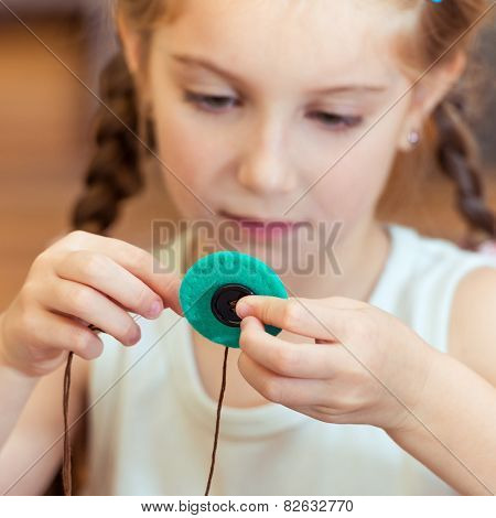 happy cute little girl to sew buttons