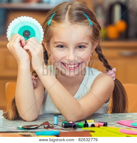 happy cute little girl shows  materials for needlework