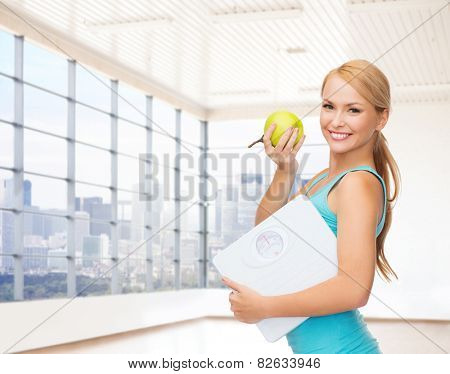 fitness, technology, people and sport concept - smiling woman with scale and green apple over gym or home background