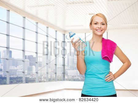fitness, sport, training, drink and people concept - happy woman with bottle of water and towel over gym or home background