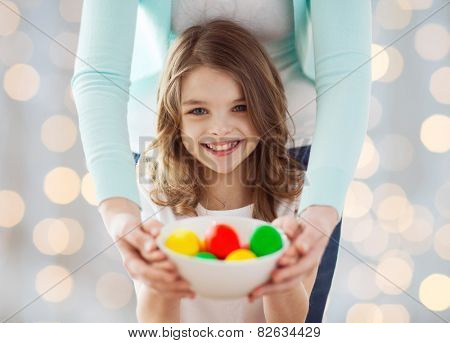 easter, family, people, holiday and childhood concept - close up of happy girl and mother hands holding bowl with colored eggs over lights background