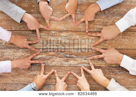 business, people, gesture and team work concept - close up of creative team showing victory hand sign on table in office
