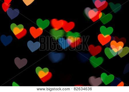 red and green heart bokeh on dark background