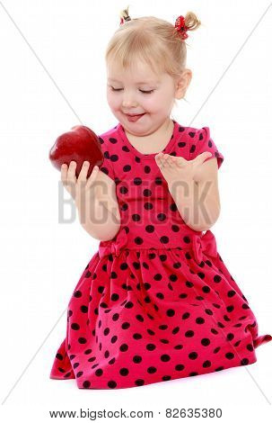 Funny little girl looks at a delicious red apple.