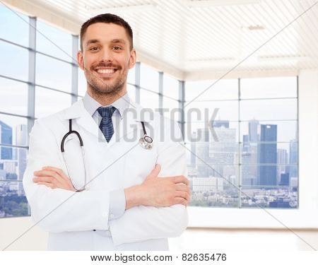 healthcare, profession, people and medicine concept - smiling male doctor with stethoscope in white coat over clinic room background