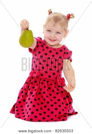 portrait of a little blonde with pear in hand.
