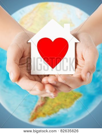 people, love, health, environment and charity concept - close up of human hands holding paper house with red heart over earth globe and blue background