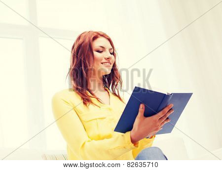 home, reading and education concept - young woman reading book at home