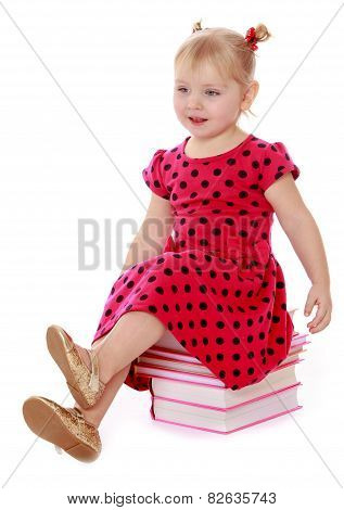 Charming little schoolgirl sitting on a stack of books.