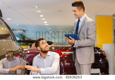 auto business, car sale, technology and people concept - happy man and car dealer with tablet pc computer talking in auto show or salon