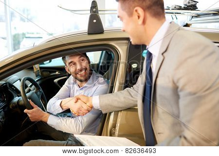 auto business, car sale, consumerism, gesture and people concept - happy man with car dealer making deal and shaking hands in auto show or salon