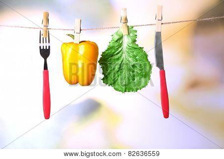 Fork, knife and vegetables  hanging from clothesline on color background
