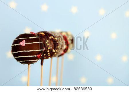 Tasty cake pops on blue background