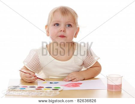 Closeup of a smart little girl draws paint sitting at the table.