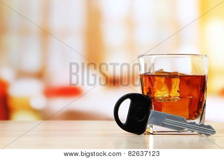 Composition with car key and glass of whiskey, on wooden table, on bright background