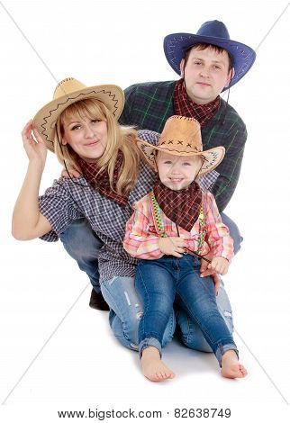 Happy young family in cowboy clothes.