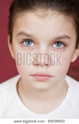 studio portrait of a pretty little girl on a burgundy background