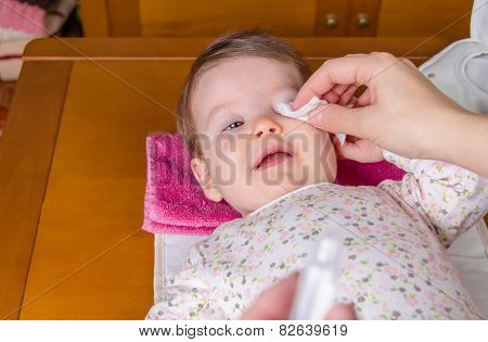 Mother hands cleaning eyes of baby with cotton