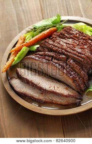 barbecue beef brisket isolated on brown wooden board