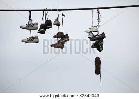 PRAGUE, CZECH REPUBLIC - APRIL 6, 2013: Old boots hang on an electrical cable in Letna, Prague, Czech Republic. According to legend, teenagers throw shoes on the cable, when they lose their virginity.