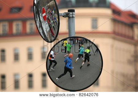 PRAGUE, CZECH REPUBLIC - APRIL 6, 2013: Convex mirrors with the reflection of athletes running a marathon run in Prague, Czech Republic.