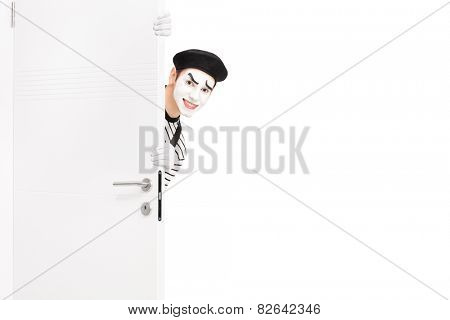 Smiling mime artist posing behind a wooden door isolated on white background