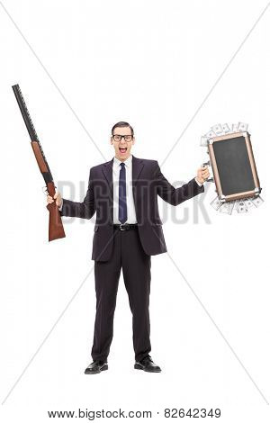 Full length portrait of an angry businessman holding a rifle and a bag full of money isolated on white background