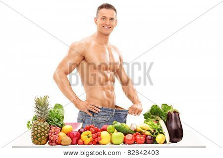 Handsome man posing behind a table with vegetables isolated on white background