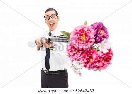 Joyful man shooting flowers from a shotgun isolated on white background