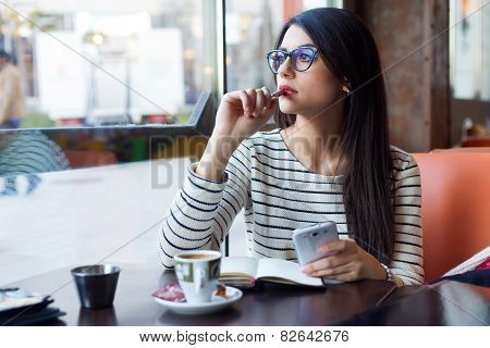 Young Beautiful Woman Using Her Mobile Phone In Coffee.