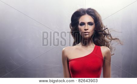 Portrait of a young and beautiful woman with a curly face. Red dress, iron background.