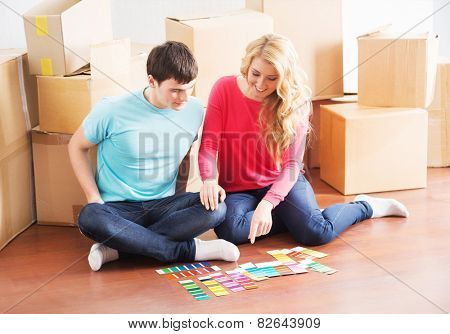 Young couple moving in a new home. Wife and husband selecting a new color for a condo.