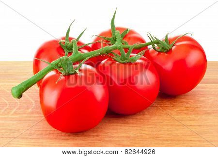 Red Tomatoes On A Branch On Wooden Board