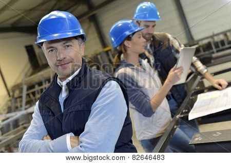 Supervisor in factory with employees in background