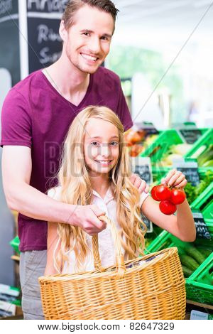 Father and daughter selecting vegetables while grocery shopping in organic supermarket