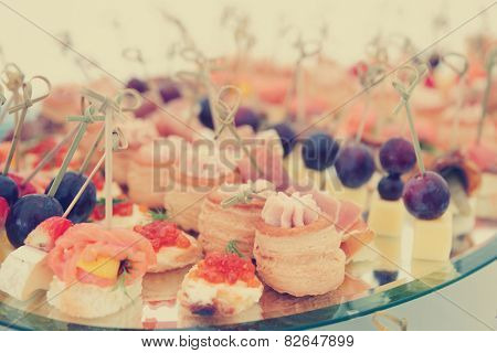 Meat, fish and cheese banquet snacks on banquet platter, toned image
