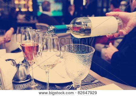 Waiting is pouring white wine in restaurant, toned image