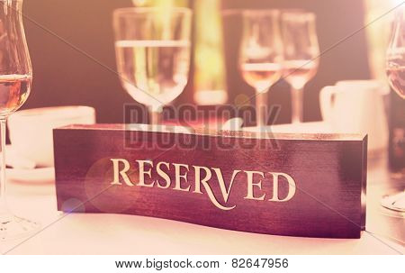 Wooden reserved plate on an arranged restaurant table, toned image