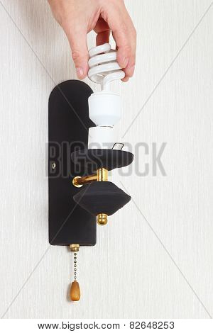 Hand unscrews tungsten bulb in a lamp on white wall