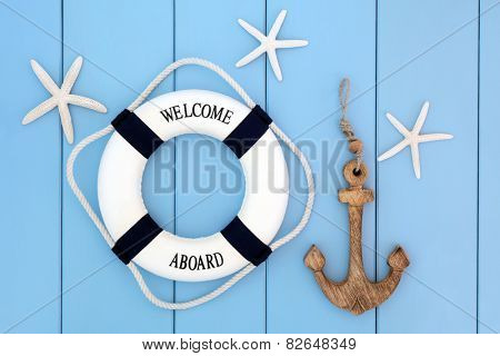 Decorative lifebuoy, anchor and starfish sea shells over wooden blue background.