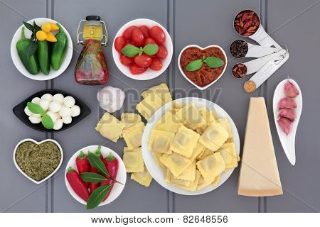 Italian and mediterranean food ingredients over grey wood background.