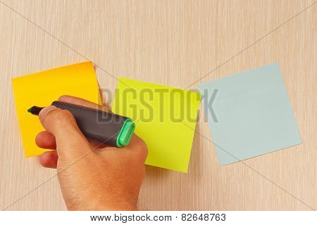 Hand writes a green marker on the sticker on wooden message board
