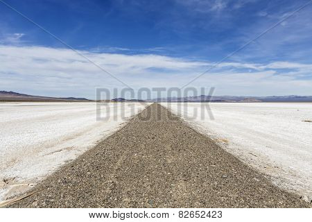 Old closed road crossing vast salt flat dry lake in California's Mojave National Preserve.