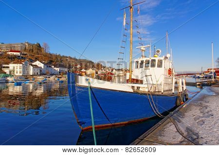 Blue Fishing Boat With A Wooden Mast