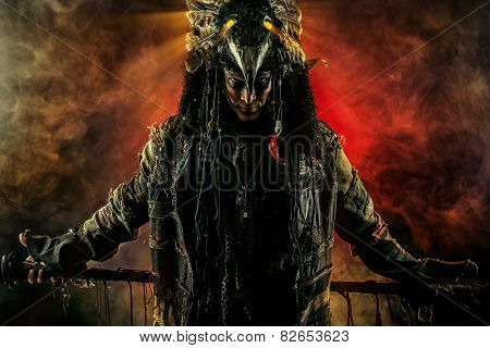 Portrait of a male shaman in ethnic dress surrounded by fog. Fantasy concept, magic.