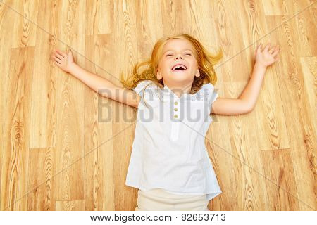 Cute joyful girl lying on a floor at home.