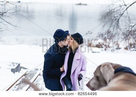 Happy couple walking the dog in a winter landscape