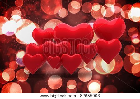 Love hearts against twinkling red and orange lights